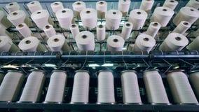 De roterende machines werken bij een textielfabriek, die clews met witte draad spinnen stock video