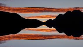 De roterende oranje lange tijdspanne van de wolkentijd over zwarte bergprofiel weerspiegelde fantasie stock videobeelden