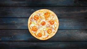 De roterende pizza met plakken van tomaten plet ui en paprika op een donkere achtergrond De hoogste richtlijn van het meningscent stock videobeelden