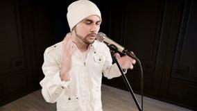 De rots van de Frontmanvocalist pop met een modieuze baard in witte kleren en een hoed met een microfoon in zijn handen expressiv stock footage