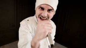 De rots van de Frontmanvocalist pop met een modieuze baard in witte kleren en een hoed met een microfoon in zijn handen expressiv stock video