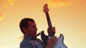 De rots van het gitaristspel in de zonsondergang op de warme zomer stock videobeelden