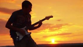 De rots van het gitaristspel in de zonsondergang op de warme zomer stock video