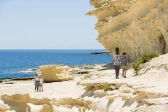 De rotsachtige kust van Malta, familiegang langs het strand Royalty-vrije Stock Foto's