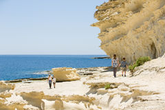 De rotsachtige kust van Malta, familiegang langs het strand Stock Foto