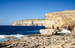 De rotsachtige kustlijn en het overzees deden ineenstorten dichtbij Azuurblauw venster in Dwejra-Baai, Gozo-eiland, Malta stock fotografie