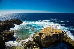 De rotsachtige kustlijnklippen deden ineenstorten dichtbij Azuurblauw venster, Gozo-eiland, stock fotografie