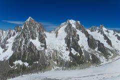De rotsachtige rand van de sneeuwberg in Alpen stock foto's