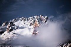 De rotsachtige top van Onderstelkap is behandeld en begraven met sneeuw in mystieke wolken stock foto's