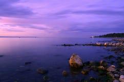 De rotsen dichtbij de kust in de zonsondergang Stock Foto's