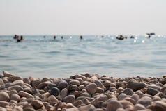 De rotsen op de kustmensen baden in het overzees Stock Foto's