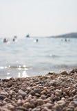 De rotsen op de kustmensen baden in het overzees Stock Fotografie