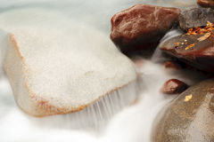 De rotsen van de rivier en melkachtig water stock afbeeldingen