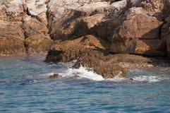 De rotsen van het eiland die hevig door het water worden geraakt stock afbeelding