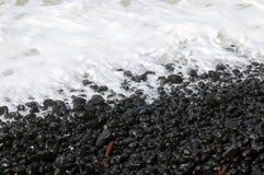 De rotsen van het strand in overzees schuim royalty-vrije stock afbeeldingen