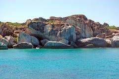 De rotsgezicht van het graniet en turkooise wateren Stock Afbeeldingen