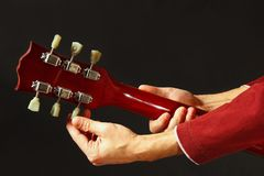 De rotsgitarist stemt de gitaar op donkere achtergrond royalty-vrije stock foto's