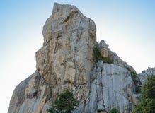 De rotsklimmer beklimt tot de bovenkant van een berg bij zonsondergang in de Krim royalty-vrije stock afbeeldingen