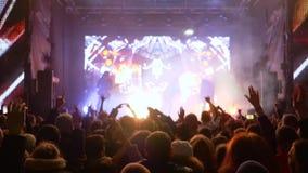 De rotspartij, menigte van stuiterende ventilators met wapens geniet omhoog van prestaties van muzikale kunstenaar op helder stad stock videobeelden