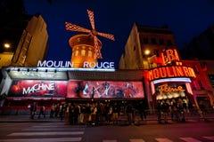 De rouge Moulin 's nachts in Parijs, Frankrijk Stock Fotografie