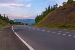 De route tussen de aarden heuvels waarlangs een grote vrachtwagen over lange afstand reist royalty-vrije stock foto's