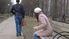 De rover draagt de vrouwen` s zak van de bank in het park stock video