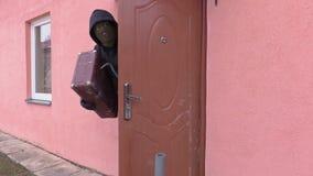 De rover met koevoet verlaat het huis met gestolen bezit stock videobeelden