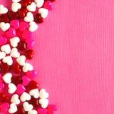 De roze achtergrond van de Valentijnskaartendag met de grens van het suikergoedhart stock afbeelding
