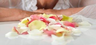 De roze en gele bloemblaadjes in vrouw overhandigen witte achtergrond Royalty-vrije Stock Afbeeldingen