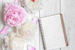 De roze en witte pioenbloemen met spatie voerden notitieboekje op witte houten lijst stock foto's