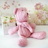 De roze gebreide teddybeer zit op een plank Stock Afbeelding