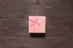 De roze giftdoos is op de houten achtergrond met lege ruimte Stock Foto