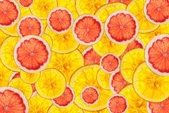 De roze grapefruits en de sinaasappelen mengen kleurrijke gesneden vruchten backgro Stock Fotografie