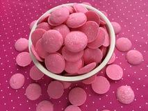 De roze Smeltingen van het Chocoladesuikergoed op roze stippenachtergrond Royalty-vrije Stock Afbeeldingen
