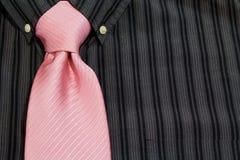 De roze stropdas die op zwarte wordt gebonden pinstriped overhemd Stock Foto's