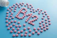 De roze tabletten in de vorm van vitaminen B12 in het hart op een blauwe achtergrond, die van een wit wordt gemorst kunnen laag t royalty-vrije stock afbeeldingen