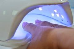De roze vingers van het gelpoetsmiddel droogt in ultraviolette lampclose-up royalty-vrije stock foto