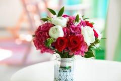 De rozen en de pioenen van het huwelijksboeket in glasvaas op lijst Stock Foto