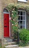 De rozen van de het plattelandshuisjedeur van het land Stock Foto