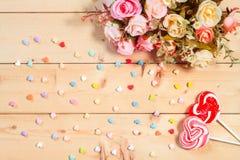 De rozenbloemen van de pastelkleurtoon met het suikergoed van de hartvorm op woode Stock Afbeeldingen