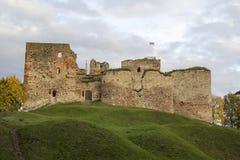 De ruïnes van het Livonia-Ordekasteel werden gebouwd in het midden van de 15de eeuw Bauska Letland in de herfst Letse vlag op aan Stock Afbeeldingen