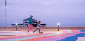 De ruïnes van het Westenpijler, Brighton, East Sussex, het UK In de en voorgrond, vage kinderen die spelen lopen Gefotografeerd b stock afbeelding