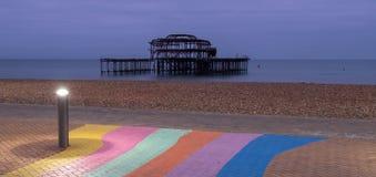 De ruïnes van het Westenpijler, Brighton, East Sussex, het UK In de voorgrond, de het kiezelsteenstrand en bestrating in regenboo stock fotografie