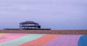 De ruïnes van het Westenpijler, Brighton, East Sussex, het UK In de voorgrond, de het kiezelsteenstrand en bestrating in regenboo royalty-vrije stock foto