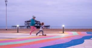 De ruïnes van het Westenpijler, Brighton, East Sussex, het UK In de voorgrond, de kinderen spelen en bestrating in regenboogstrep royalty-vrije stock afbeeldingen