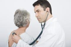 De Rug die van artsenchecking patient Stethoscoop met behulp van Stock Foto