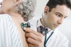 De Rug die van artsenexamining patient Stethoscoop met behulp van Stock Fotografie