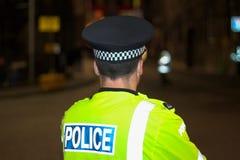 De Rug van de politieagent, na Schemer, Duisternis Royalty-vrije Stock Afbeeldingen