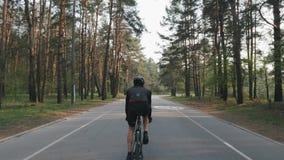 De rug volgt schot van geschikte sportieve fietser in zwarte uitrustings berijdende fiets Benen met sterke spieren die fiets het  stock footage