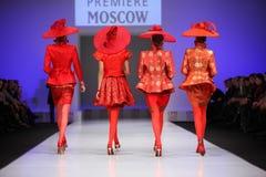 De ruggen van vier vrouwen lopen de loopbrug Stock Foto's